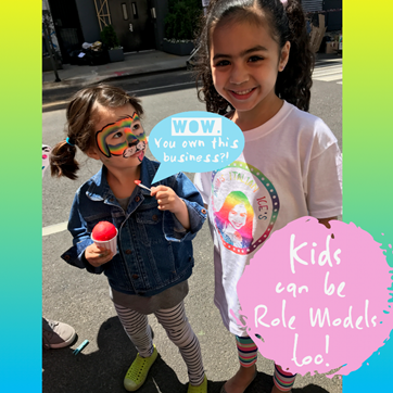 child-eating-italian-ice-and-looking-up-to-kidpreneur-indias-italian-business-owner-and-role-model-at-childrens-museum-of-the-arts-block-party-rainbow-dog-face-paint-kids-can-be-role-models-too