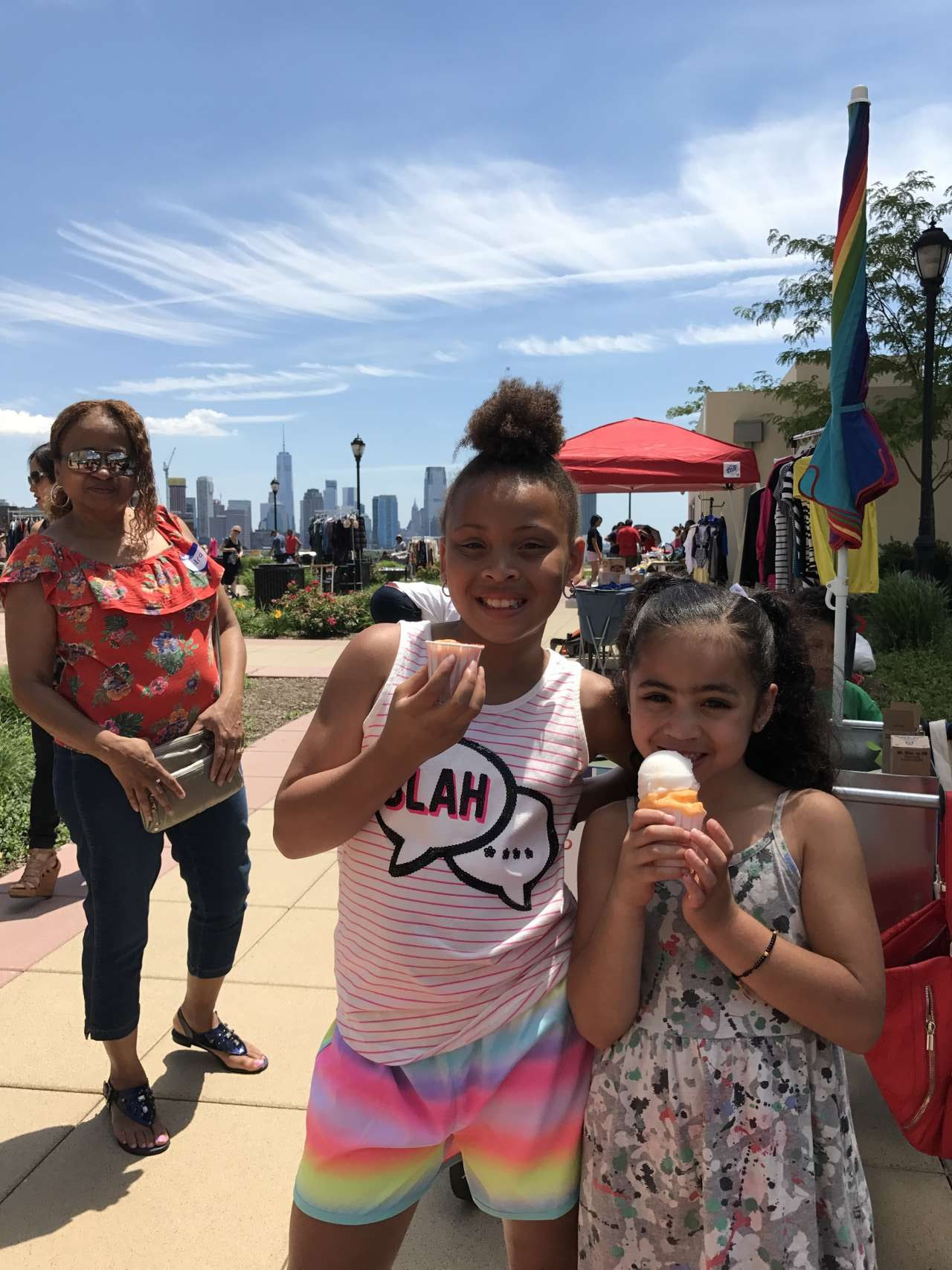 2 girls eating Italian Ice with brightly printed clothing on a summer day with NYC views in the background