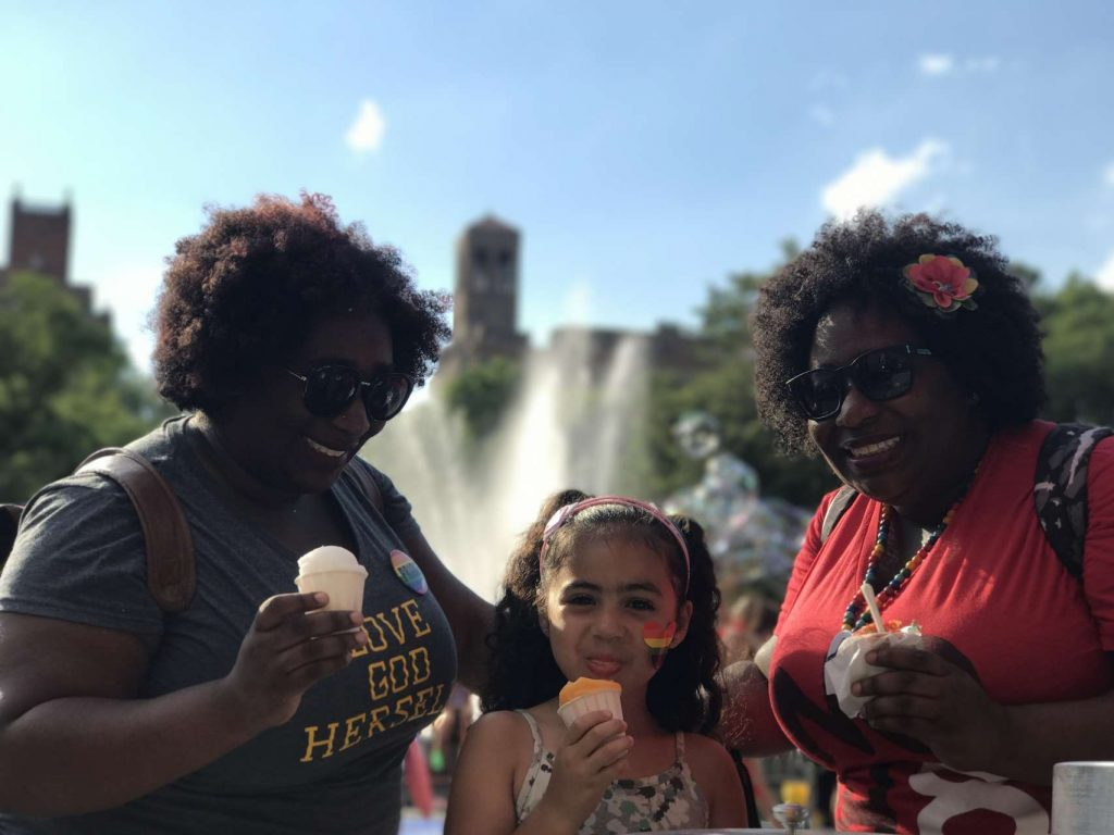 India Jolie girl sticking out tongue eating ices standing in between two women twins with curly afros eating Indias Italian Ice