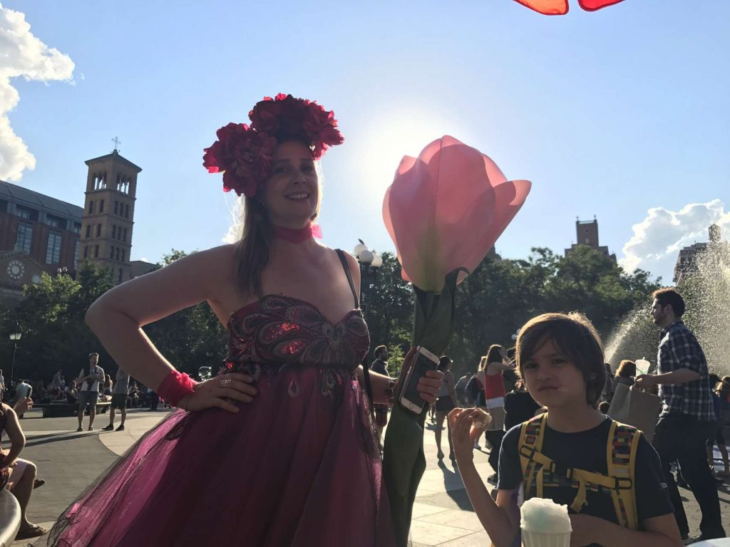 Women holding oversized dramaatic pink flower wearing flower headband and pink dress next to boy eating italian ice in park
