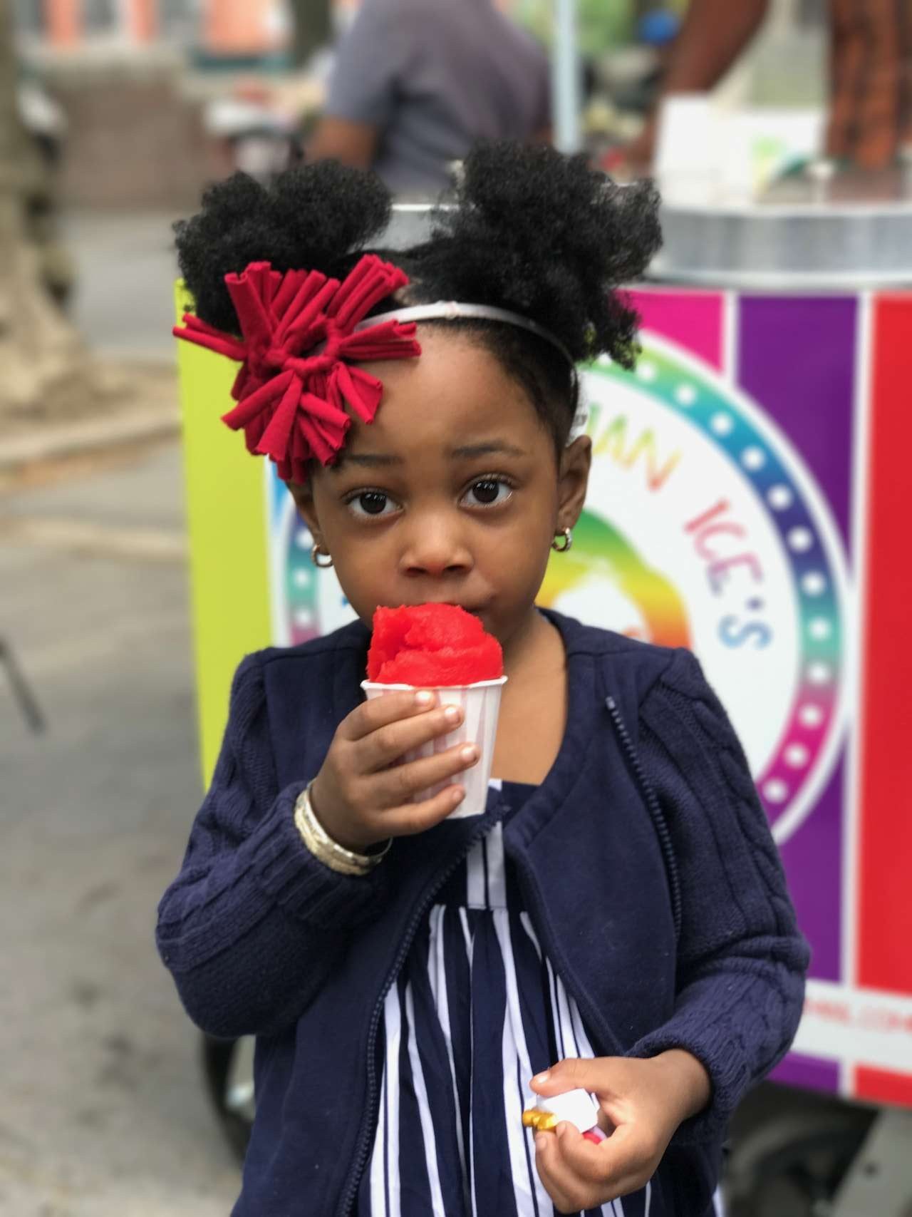 little girl with afro puff ponyails holding cherry red italian ice and wearing cherry red headband in front of rainbow italian ice cart