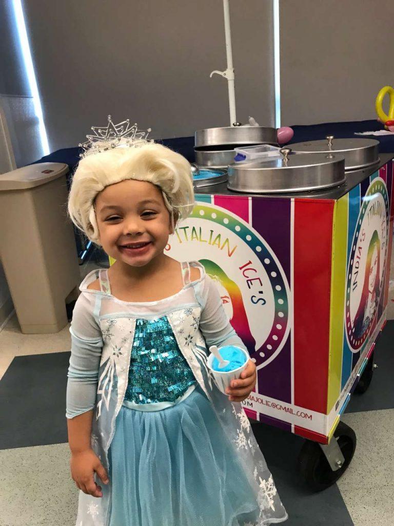girl in elsa costume eating blue italian ice