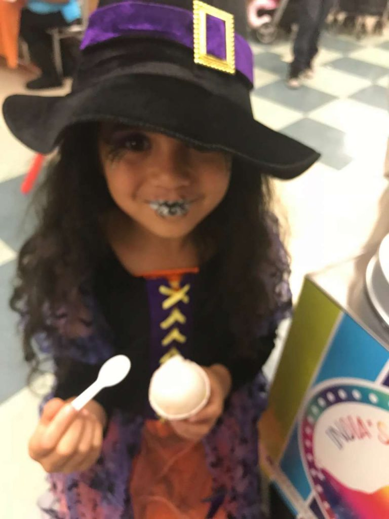 Girl eating lemon Italian ice in a witch costume