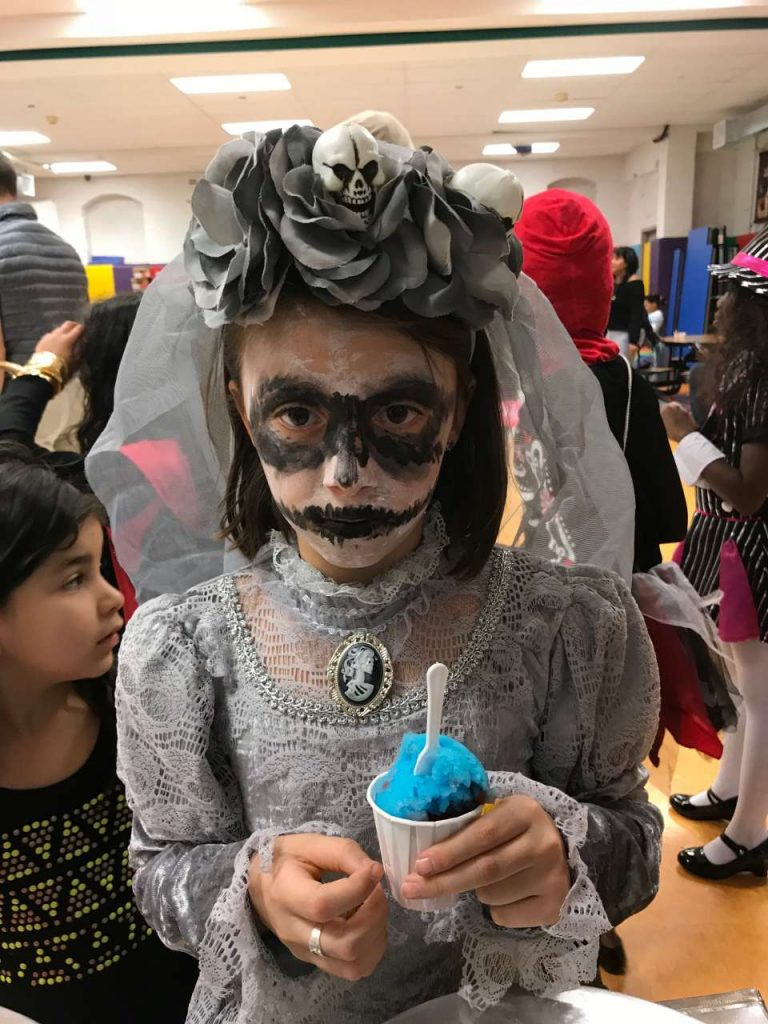 girl dressed in day of the dead grey bride costume eating blue italian ice
