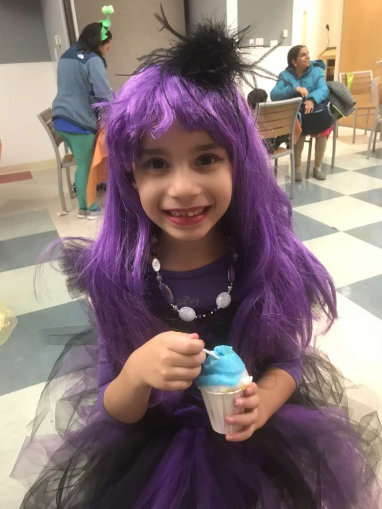 Girl in monster high purple wig costume eating blue italian ice